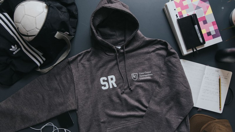 Charcoal grey leavers hoodie laid on table with school logo and student initials printed on the chest