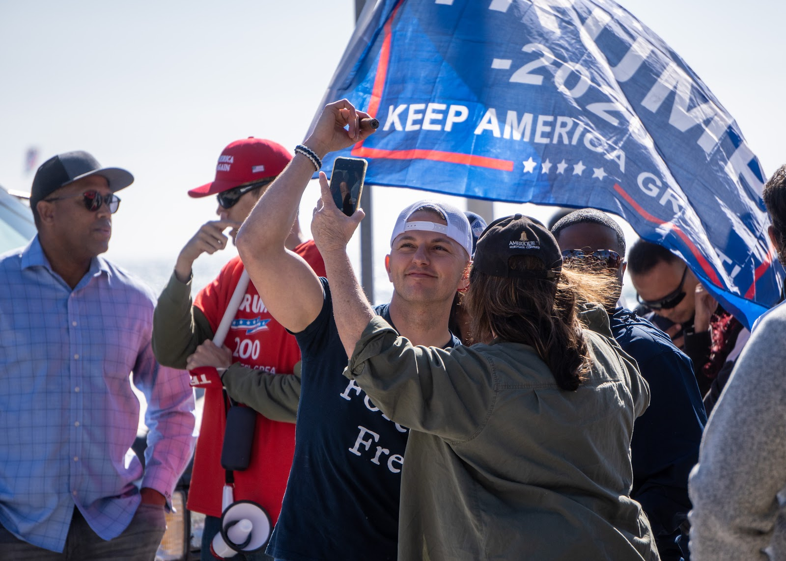 Cordie Williams poses for a video and a photo with an attendee, rhythmically swaying to the generic dance drum break being played on loop after the two speakers finished up. A trump flag flows in the breeze above his head, held by a man in a separate conversation in the background.