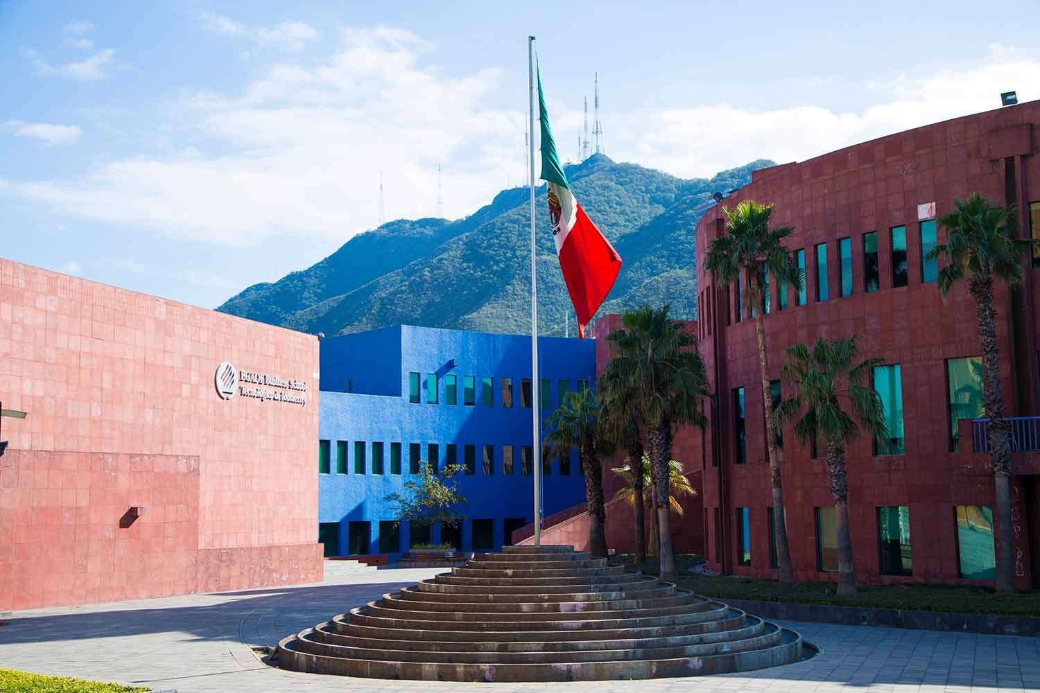 The Mexican flag waves outside the main building of the EGADE Business School with a green mountainside in the background
