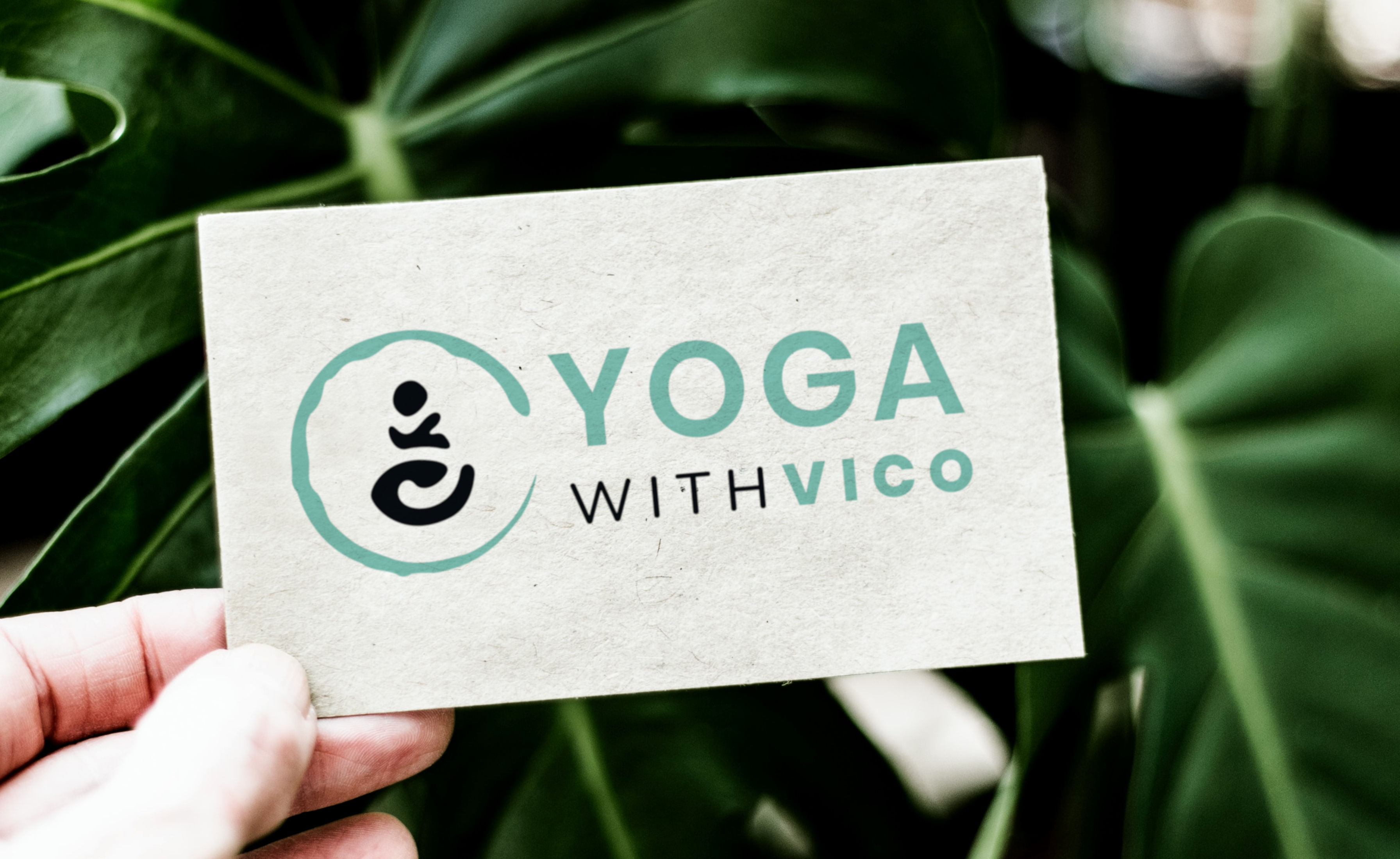 Yoga with Vico's rectangular logo design shown on a business card made from recycled paper. The card is held by a hand in front of green plant leaves.