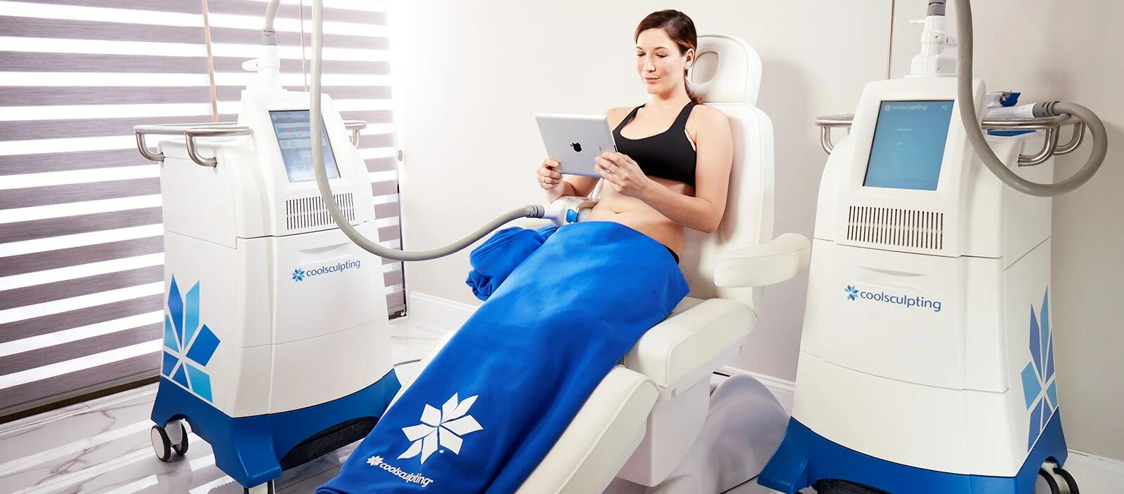 Woman sitting down and receiving CoolSculpting treatment