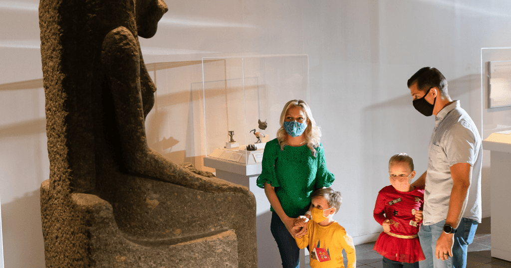 A family of four stands with masks on admiring an Egyptian statue at the San Antonio Museum of Art