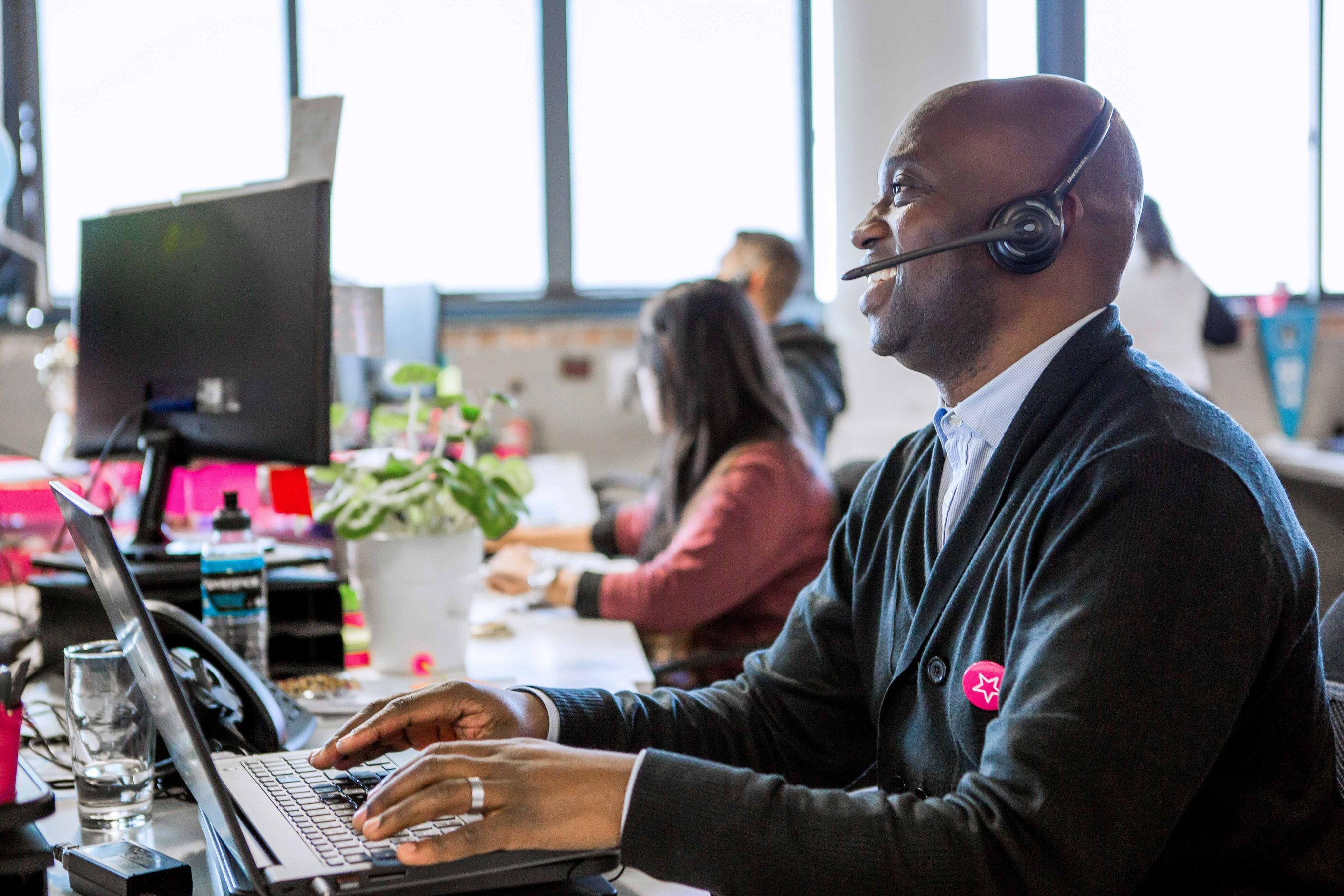 An employee in casual attire works on a laptop at their desk with pink headphones on