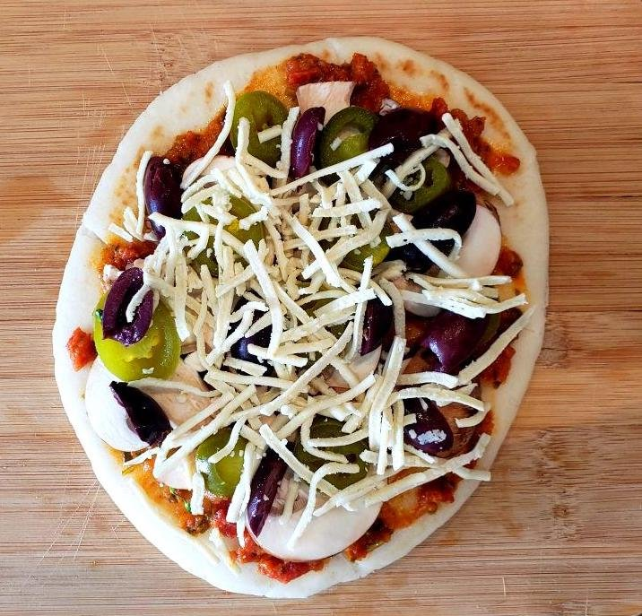 Uncooked flatbread with jalapeño, olives, and mushroom