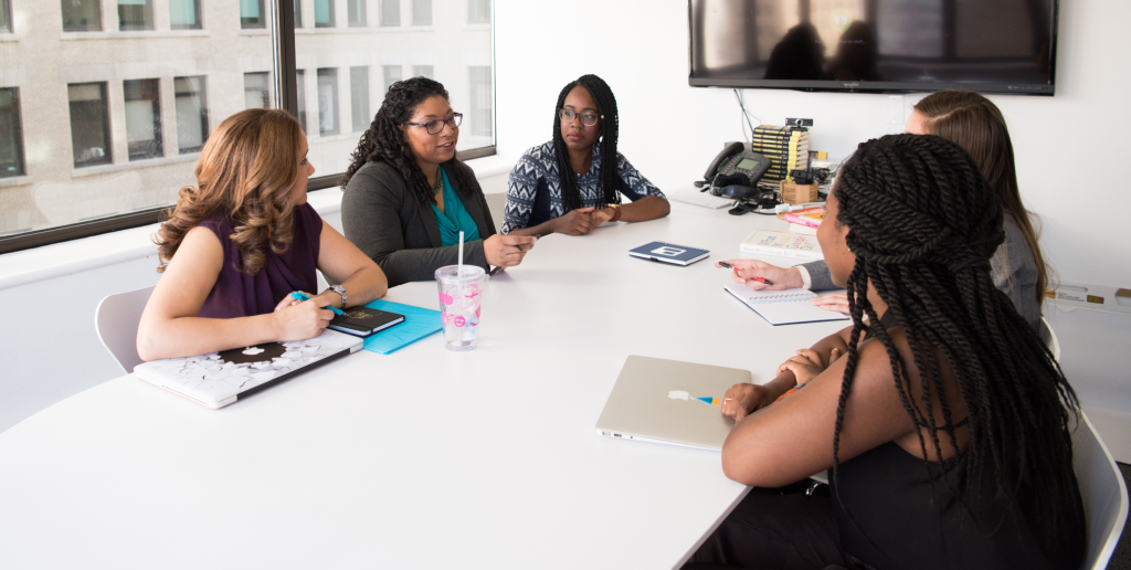 Picture of 5 women sitting around a conference room table discussing something at a meeting.