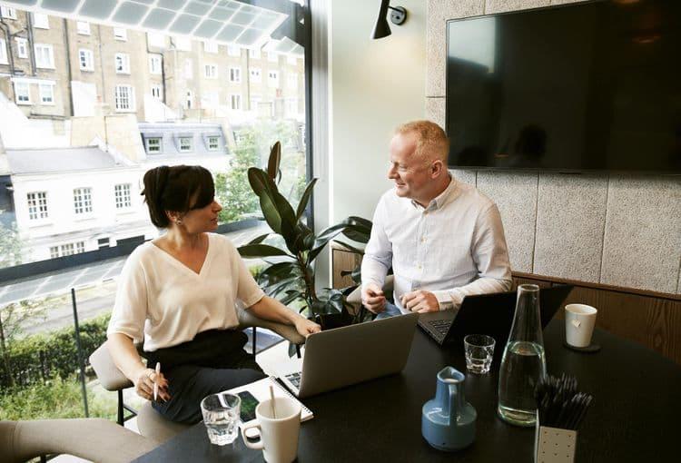 Frau und Mann an Tisch vor Laptop und Fernseher