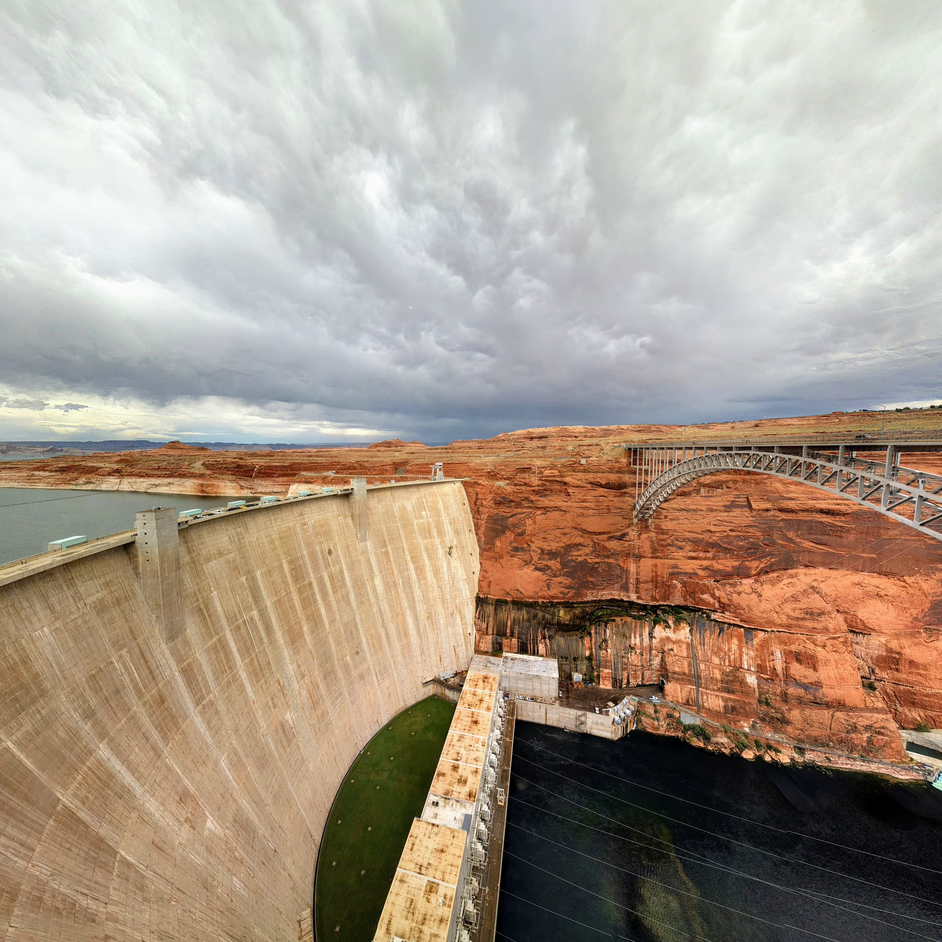 A wide-angle shot of the Glen Canyon Dam (left) and Glen Canyon Dam Bridge (right), with the Colorado River below.