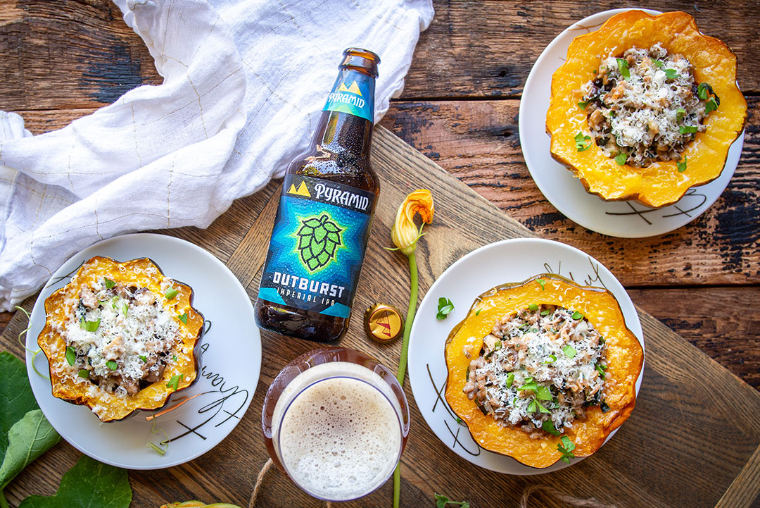acorn squashes filled with sausage and kale on plates surrounded by a bottle of Outburst IPA