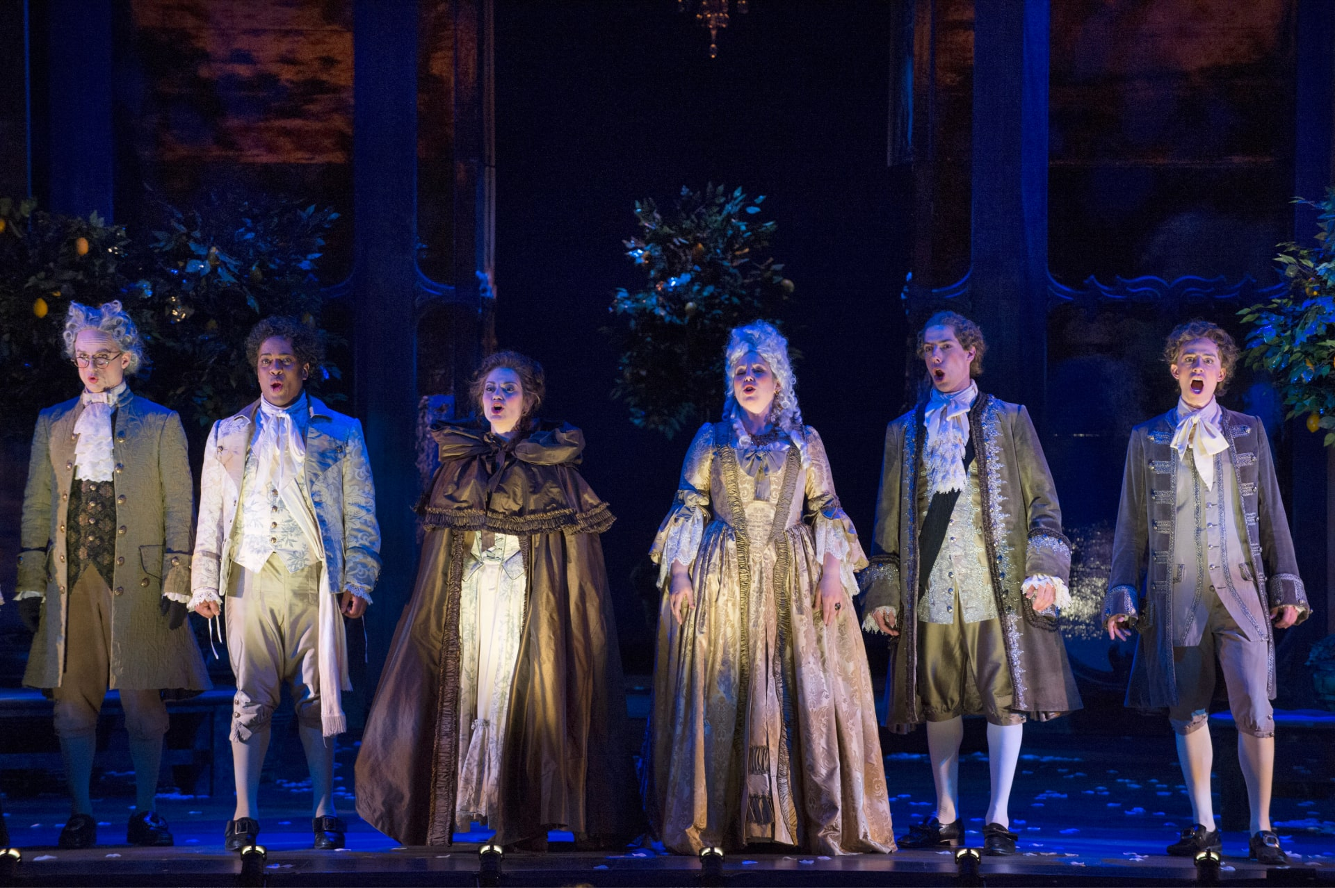 Six opera players in elaborate 18th century attire sing at the forestage lit by footlights.
