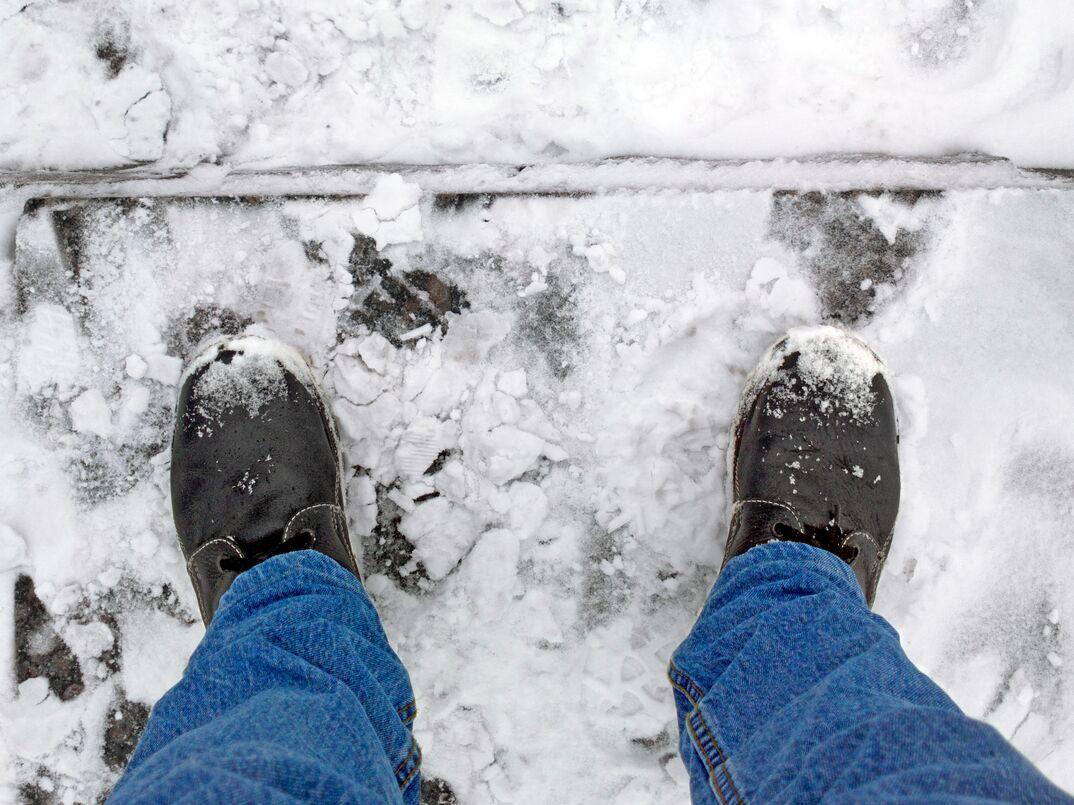 man's boots on frozen concrete steps