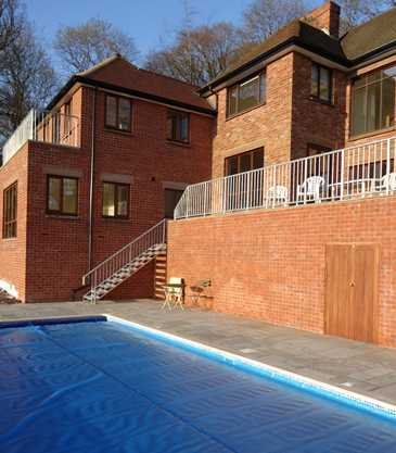A swimming pool set with surrounding slabbing and overlooked by a balcony