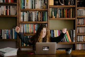 A girl celebrating learning in front of a laptop