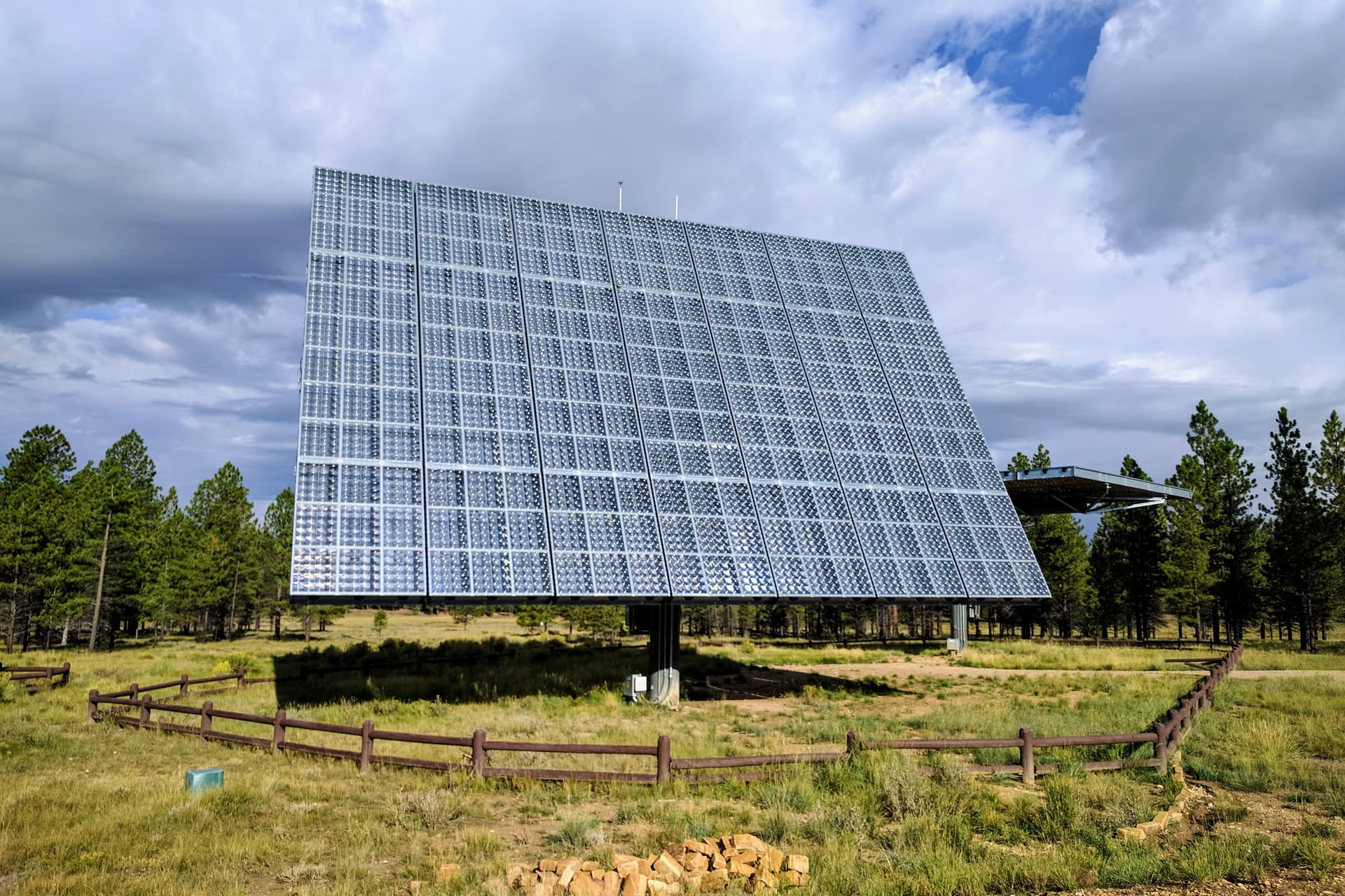 A large, free-standing solar panel in a forest clearing. Beyond it is a second panel, angled straight up as if it were a giant table.