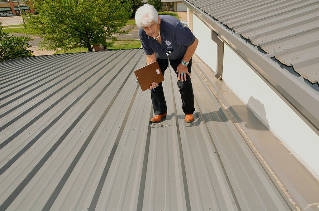 professional roofing contractor inspecting a metal roof