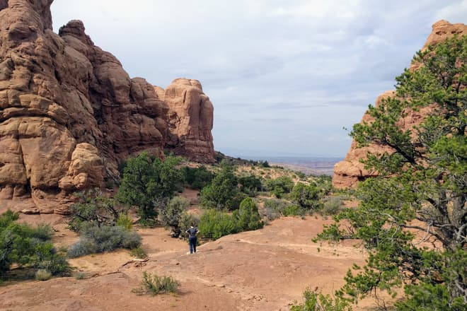 Len, in a gray shirt, stands far down a trail of red sandstone, her hands on her hips. Walls of red rock stand to her left and right, and a small grove of juniper trees is in front of her.