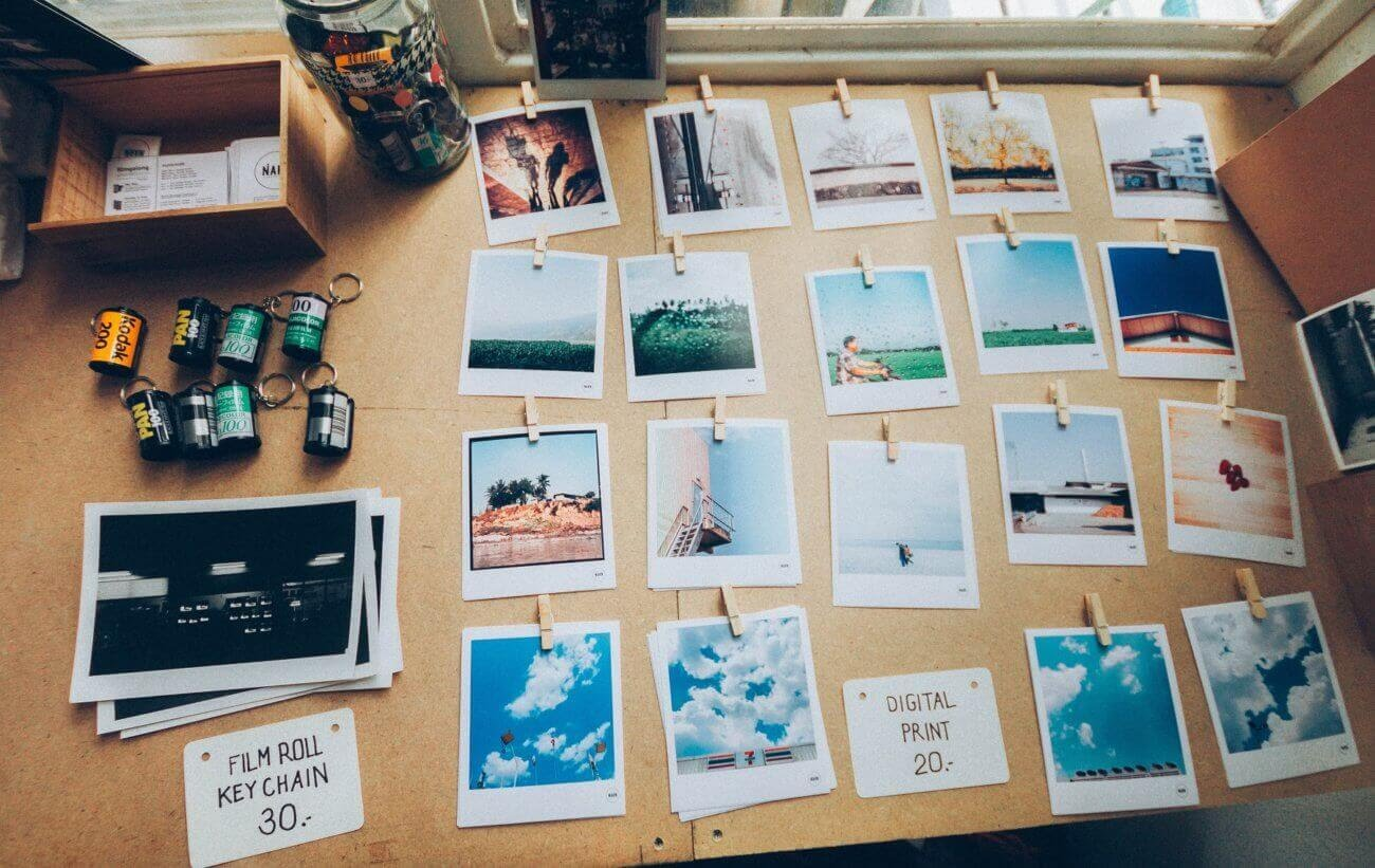 Várias fotos de polaroid presas por um prendedor e apoiadas em uma mesa.