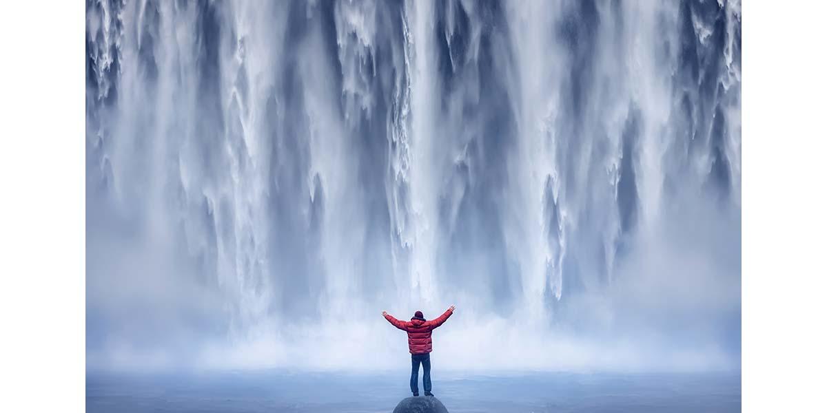 Person standing below waterfall