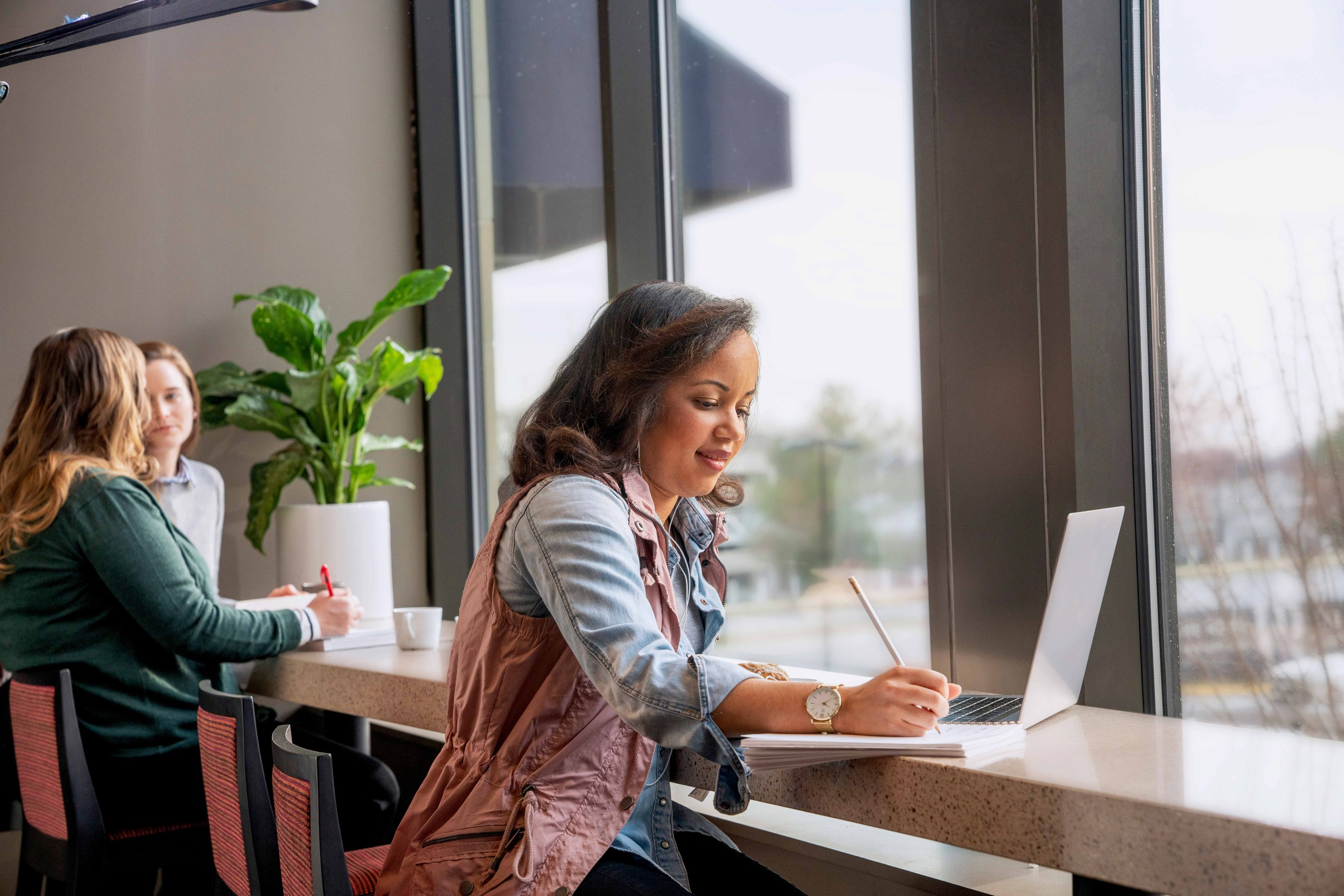A woman writes on a notepad while sitting in a cafe lounge and working on her laptop