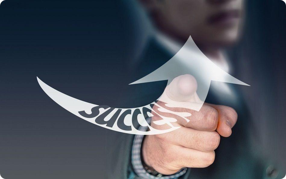 Excellence opérationnelle - L'index d'une main pointe une flèche virtuelle dans laquelle il est indiqué success