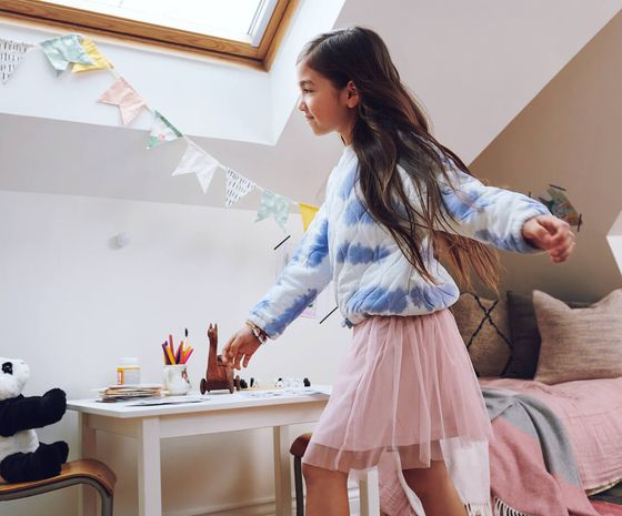 Girl dances in bedroom in front of SmartSensor affixed to wall.