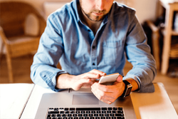 A worker typing on a phone trying to figure out what to do with his furloughed status