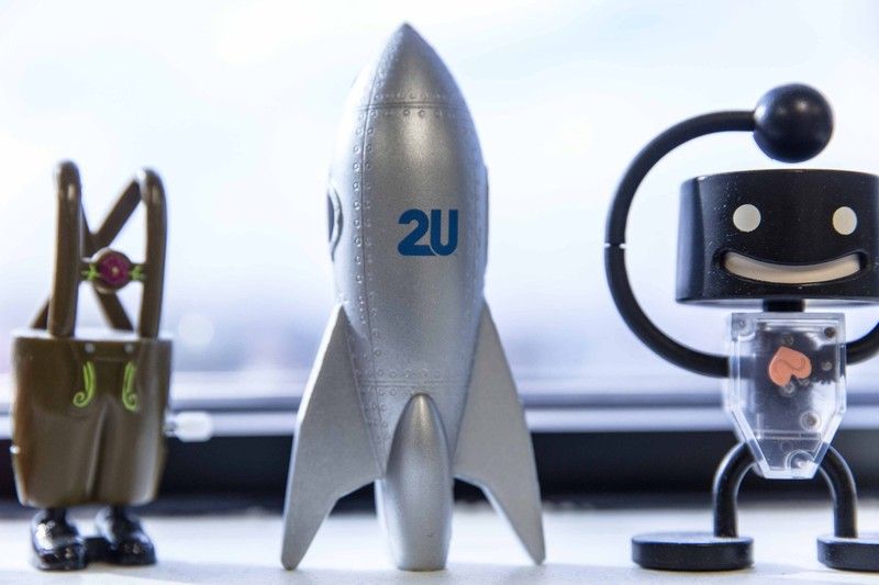 A silver rocket with the 2U logo on it sits in between a smiling robot toy and an overalls with feet toy