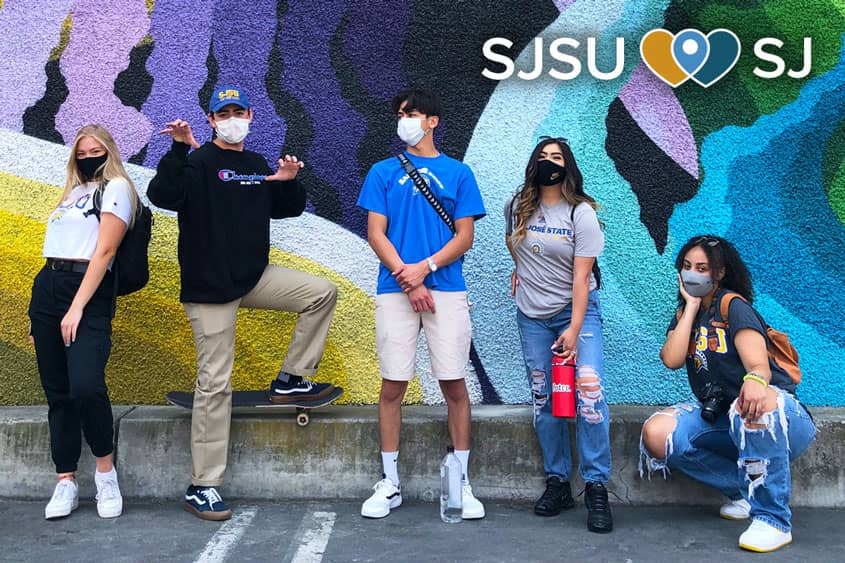 Students in SJSU gear posing in front of a colorful mural in downtown San Jose.