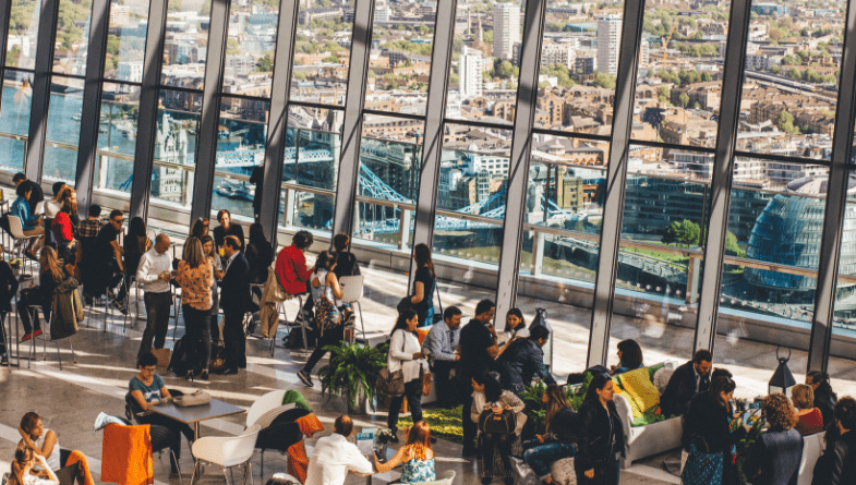 Groups of advisors or accountants or business owners stand and network at a business networking event and socialise and talk with large windows and drinks and tables and bar #networking