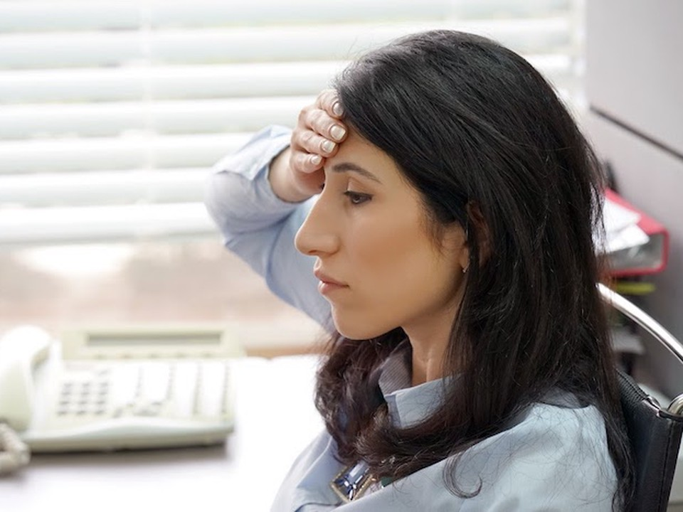 A tired social worker at her desk deals with the effects of compassion fatigue.