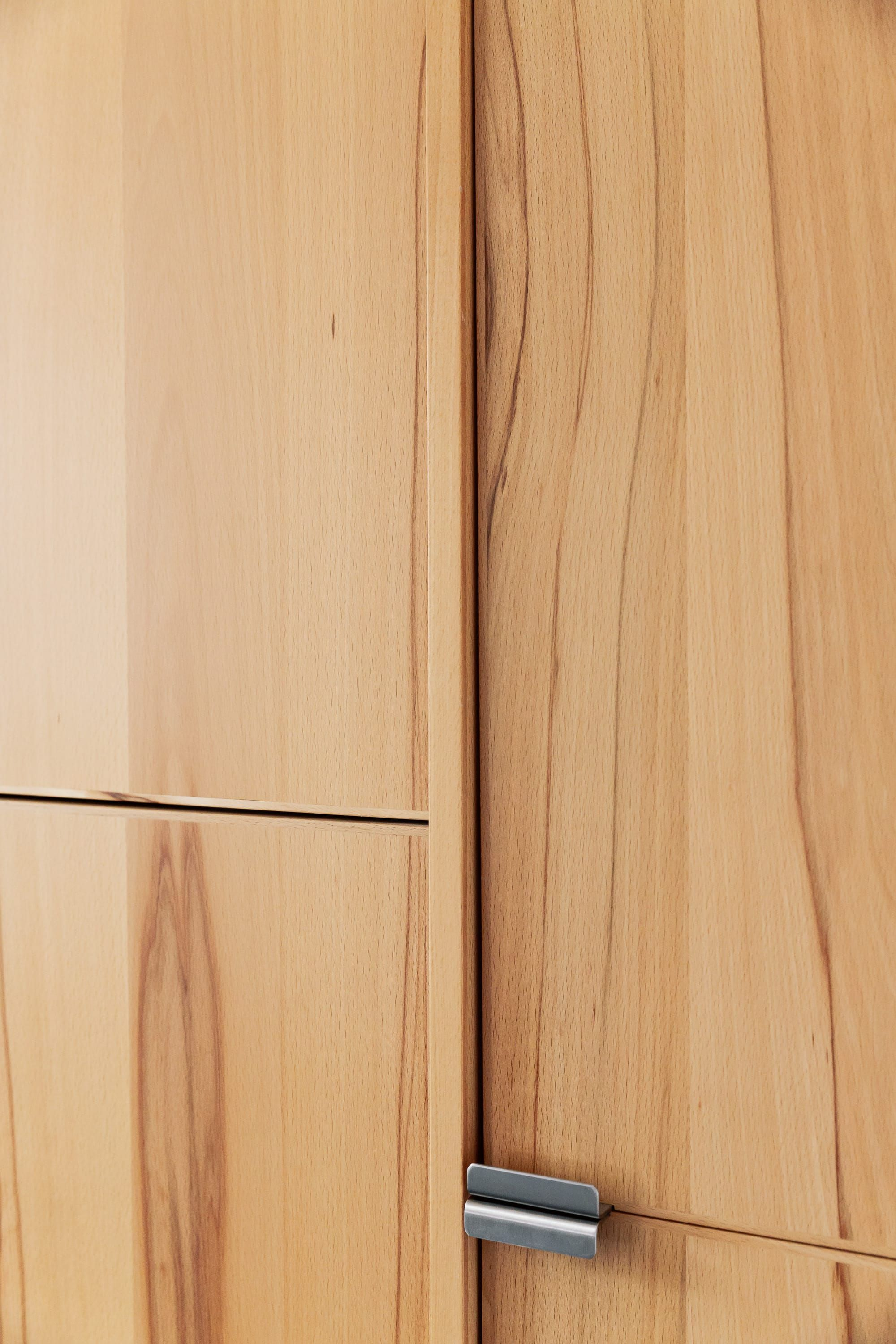 Steamed beech cabinetry with stainless steel finger pull detail.
