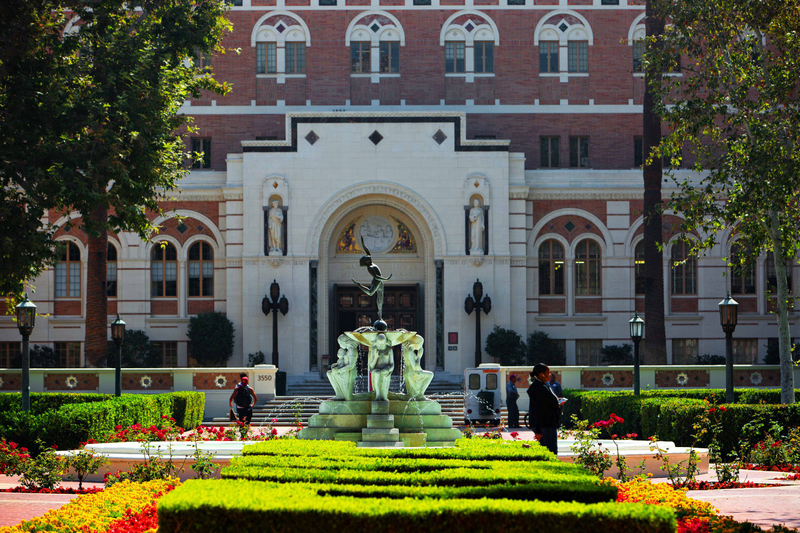 A USC campus building with a statue at the entrance and a fountain and gardens in the foreground