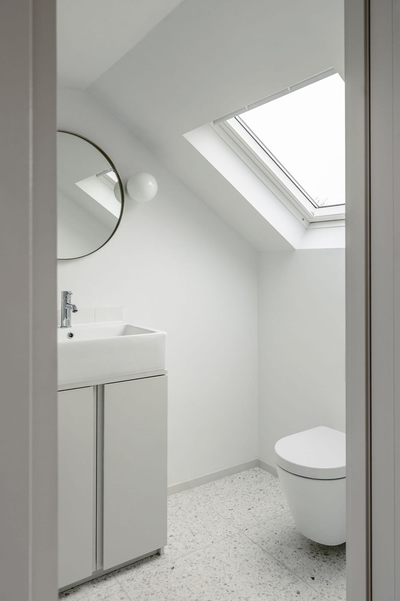 Internal view looking into the ensuite bathroom within the rear dormer extension with light grey joinery white terrazzo tiles at Northbrook Road designed by From Works.