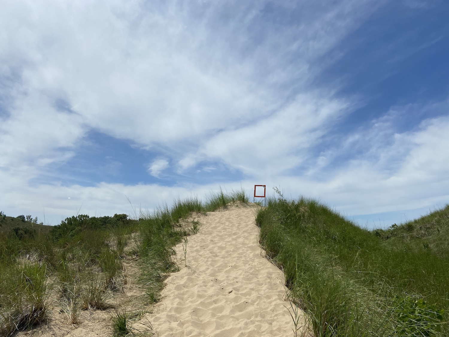 A sand dune in Michigan with an empty frame meant to hold a trail info sign on top of the dune.