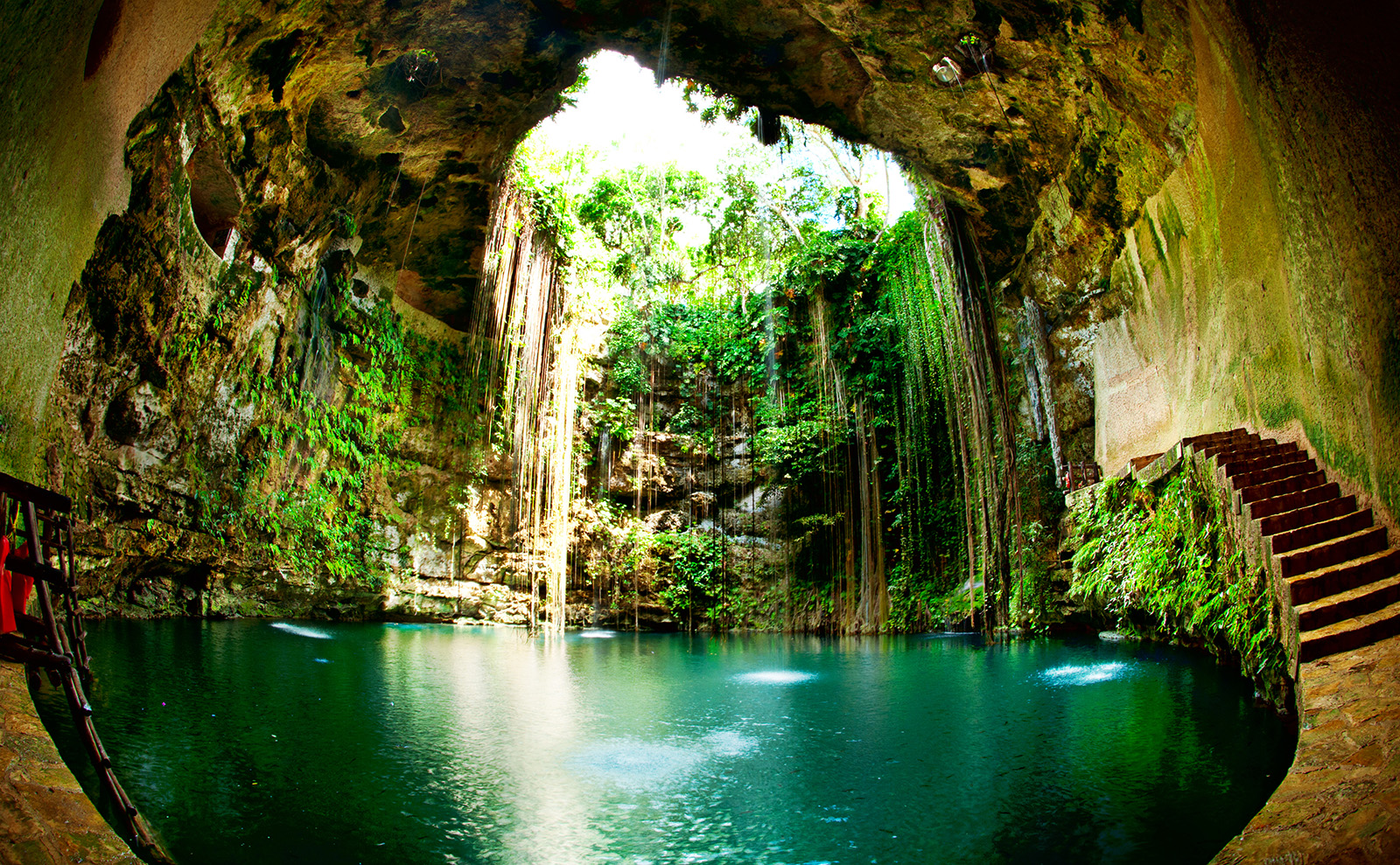 blue water in a cave with vines in Ik-Kil Cenote, Chichen Itza, Mexico