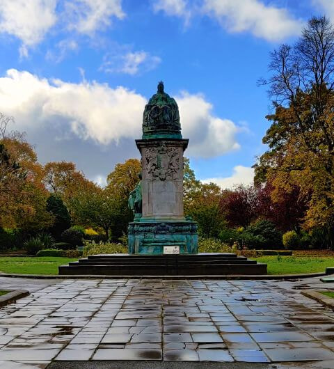 Statue at Woodhouse Moor/Hyde Park against a blue sky and wet ground