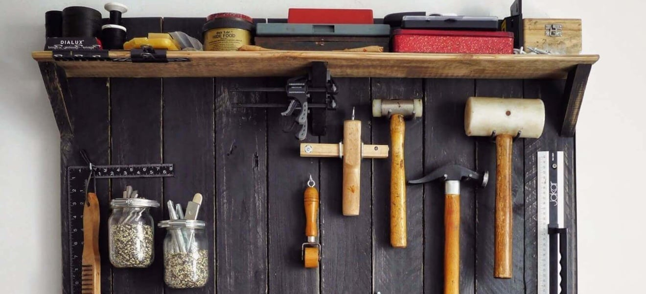 Tools hanging on a tool rack on the wall.