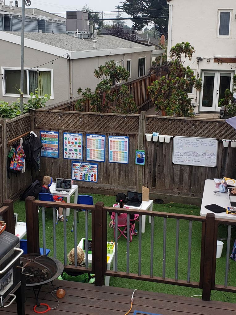 A view of the deck and the learning pod space with masked students at their desks