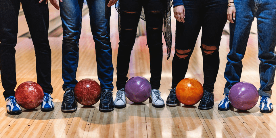 Team of staff, colleagues, from business go out for team day out bowling standing next to eachother with bowling balls in front of lanes #staff