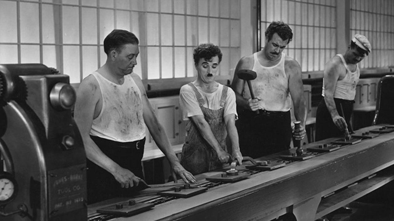Chaplin e outros trabalhadores matelando peças sem propósito claro a eles. Alienação do trabalho.