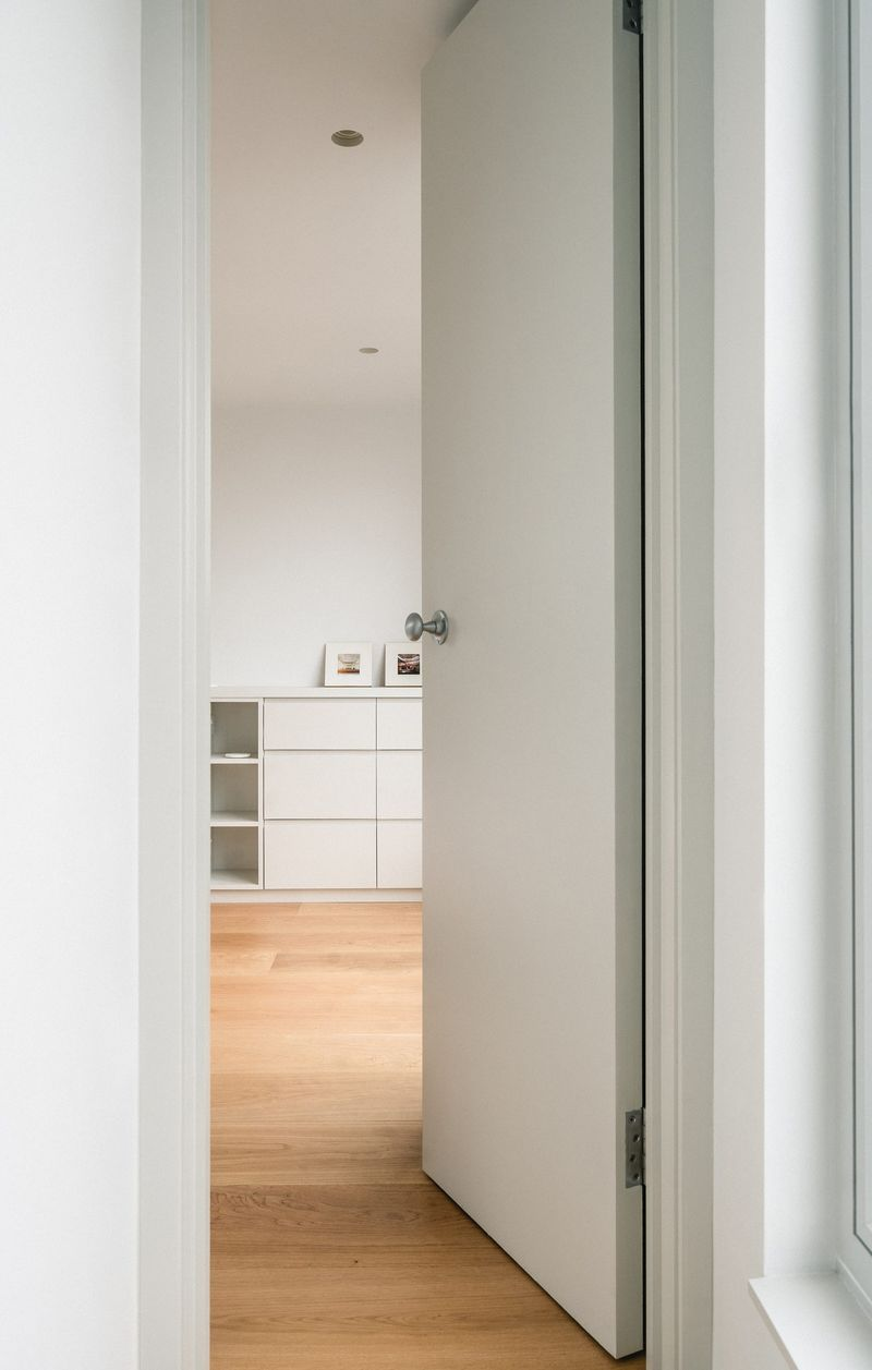 Internal view looking into the bedroom within the rear dormer extension with light grey joinery and lightweight curtains at Northbrook Road designed by From Works.