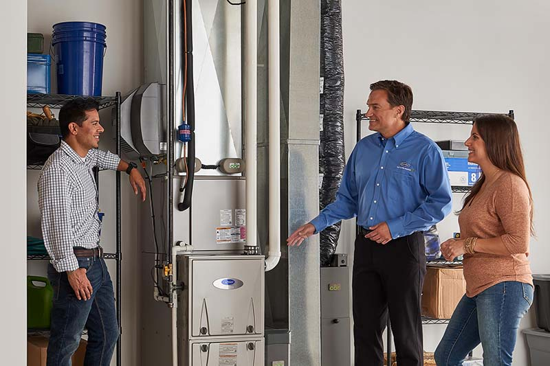 Carrier technician explaining a furnace to a younger couple
