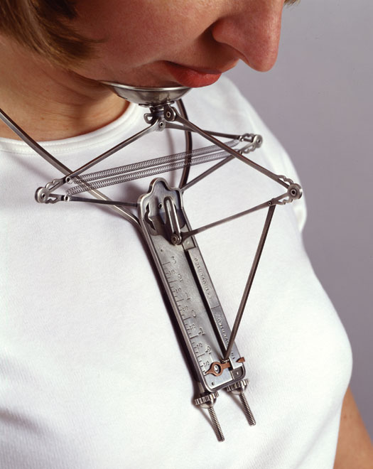 """A woman wears a metal """"necklace"""" with a measuring stick attached to a cup for her chin. The vertical measure marks the extroversion level by its distance from the relative elevation of the chin."""