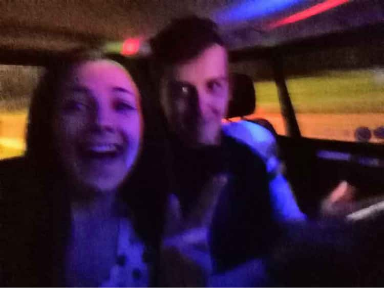 Myself and Naomi in the back of a taxi, covered in bright multi-coloured lights, posing awkwardly so that the taxi driver does not see us.
