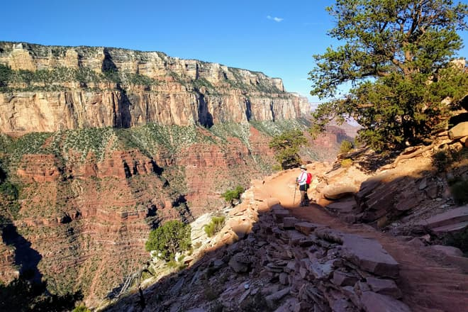 Len stands on a trail descending into the Grand Canyon from the South Rim. The shadow of the South Rim ends just before her, and in the background another part of the South Rim, composed of thick red and white sandstone bands, can be seen.