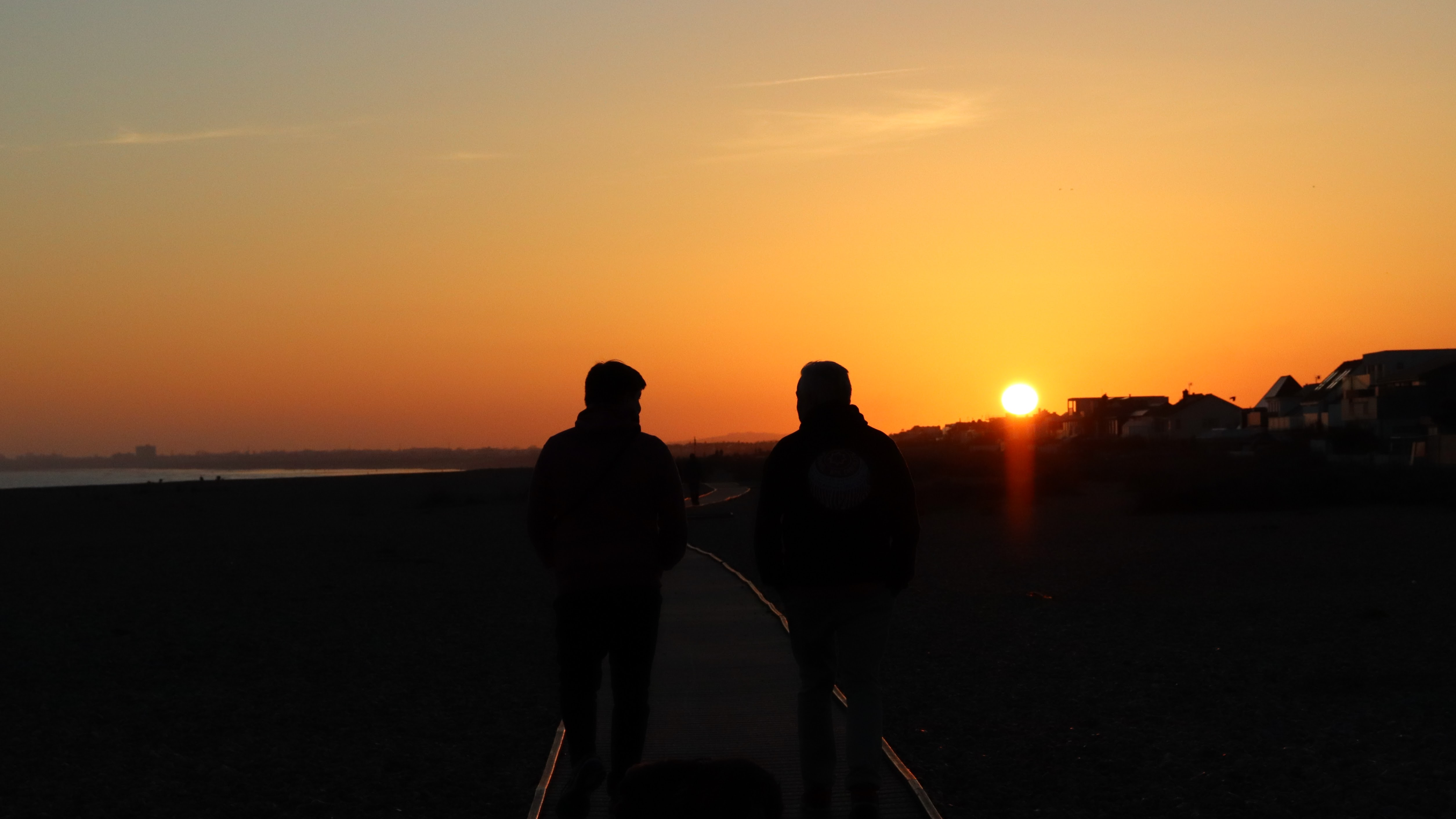 Two men walking on a board walk with orange skies behind then as the sun sets behind rooftops.