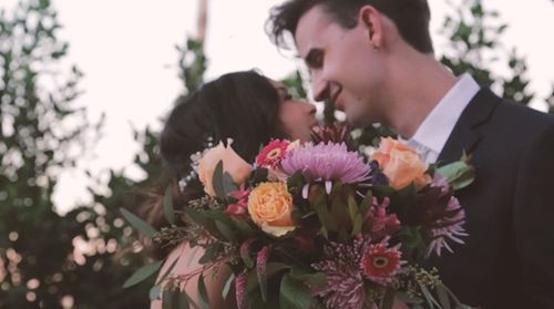 Wedding couple smiling behind bouquet