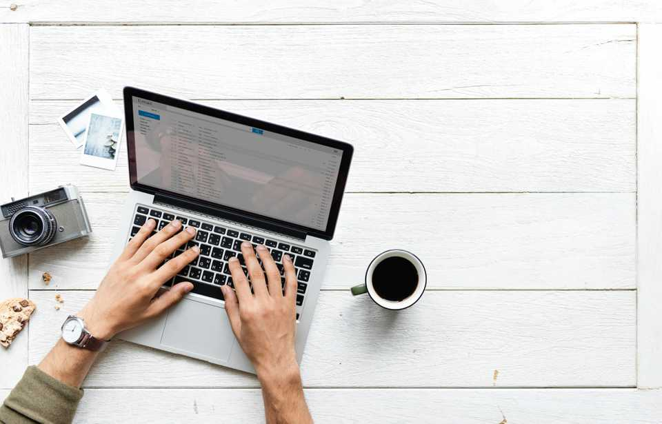 Entrepreneur typing on laptop with coffee and camera on desk.
