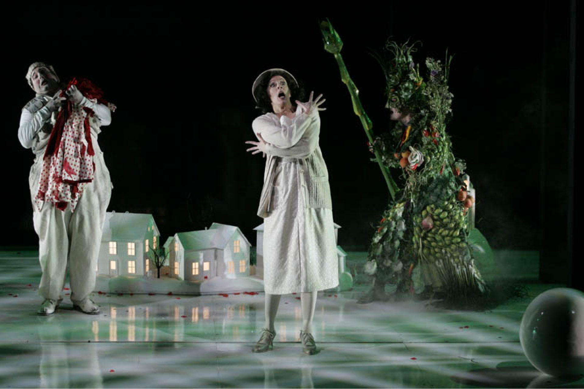 Woman in white dress and cardigan and man in checkered hat carrying red cloak stand frozen by green witch brandishing asparagus staff.