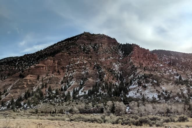 A small peak of red stone next to a mountain highway. Despite obviously being a winter scene, there is remarkably little snow on the ground.