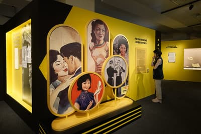 A photo of the Fashioning Identities section, with a woman looking at the information text. In the foreground, there are several circular stands featuring illustrations of glamourous women and men.